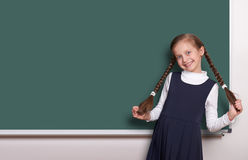 Beautiful school girl with pigtail smiled near blank chalkboard background, dressed in classic black suit, education concept Stock Photo
