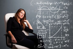 Beautiful school girl thinking about complex mathematical signs Royalty Free Stock Images