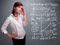 Beautiful school girl thinking about complex mathematical signs Royalty Free Stock Photos