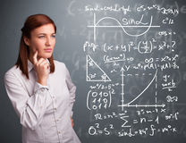 Beautiful school girl thinking about complex mathematical signs. Beautiful young school girl thinking about complex mathematical signs Stock Image