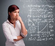 Beautiful school girl thinking about complex mathematical signs. Beautiful young school girl thinking about complex mathematical signs Stock Images