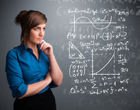 Beautiful school girl thinking about complex mathematical signs. Beautiful young school girl thinking about complex mathematical signs Royalty Free Stock Image