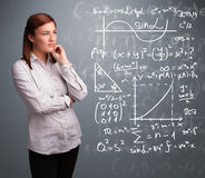 Beautiful school girl thinking about complex mathematical signs. Beautiful young school girl thinking about complex mathematical signs Royalty Free Stock Photos