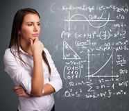 Beautiful school girl thinking about complex mathematical signs. Beautiful young school girl thinking about complex mathematical signs Stock Photo
