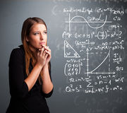 Beautiful school girl thinking about complex mathematical signs Stock Image