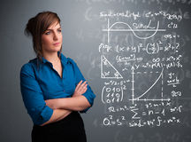 Beautiful school girl thinking about complex mathematical signs Royalty Free Stock Image