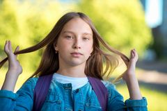Beautiful schoolgirl girl. Summer in nature after school. He adjusts his hair with gestures. Close-up of a freckle on stock photos