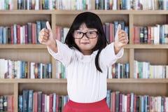 Beautiful schoolgirl in library Stock Photo