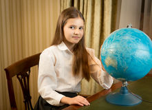 Beautiful schoolgirl posing at cabinet with Earth globe Stock Photos