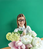 Beautiful schoolgirl in round glasses with flowers on school blackboard background. Royalty Free Stock Photo