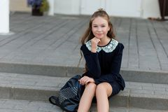 Beautiful schoolgirl in school uniform with a backpack at the sc Royalty Free Stock Images