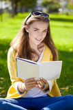 Beautiful schoolgirl sitting in autumn park and reading a book Royalty Free Stock Photo