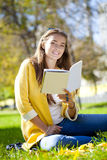 Beautiful schoolgirl sitting in autumn park and reading a book Royalty Free Stock Image
