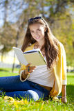 Beautiful schoolgirl sitting in autumn park and reading a book Royalty Free Stock Photography