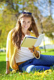 Beautiful schoolgirl sitting in autumn park and reading a book Stock Photos