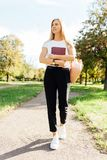 Beautiful schoolgirl walking in the Park holding a book in a goo royalty free stock photos