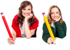 Beautiful schoolgirls posing with big pencil Royalty Free Stock Images