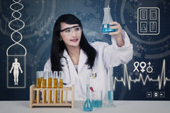 Beautiful scientist analysing solutions on blue Stock Photography