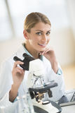 Beautiful Scientist Sitting With Microscope At Desk Stock Photography