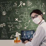 Beautiful scientist work with laptop on chalkboard background Royalty Free Stock Photos