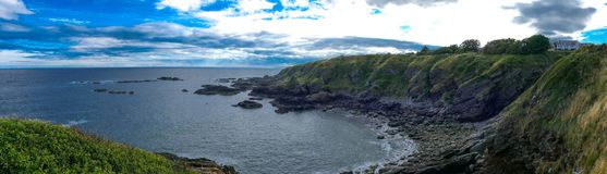 Beautiful Scotland - East Coast Panorama. East shore of Scotland, rocky beach, cliffs with white house. Aberdeen shire area panorama view stock photos
