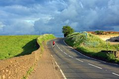 Beautiful Scottish road with a lonely cyclist i Royalty Free Stock Photos
