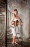 Beautiful screaming steampunk woman with whip on the stairway Stock Image