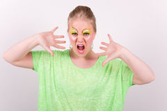 Beautiful screaming young woman with green makeup. And clothes that look straight into the camera Royalty Free Stock Photography