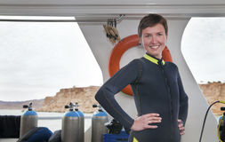 Beautiful scuba diver wears diving suit on boat Royalty Free Stock Photos