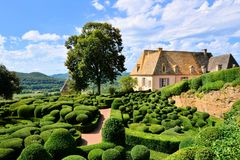 Sculpted gardens with house, Dordogne, France. Beautiful sculpted gardens with traditional house, Dordogne, France royalty free stock images