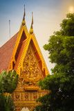 Beautiful sculpture of angel riding garuda holding naga with glass mosaic and other ornamental decoration on the gable end of bud. Dhist church at Wat Phra That stock photos