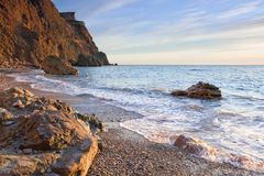 A beautiful sea beach with stones reflect sunlight Royalty Free Stock Photography