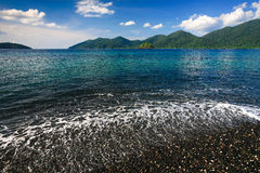 Beautiful sea and black pebble beach at tropical island Stock Image