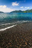 Beautiful sea and black pebble beach at tropical island Royalty Free Stock Image