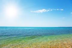 Beautiful sea and cloudy sky with sun Stock Photos