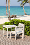 Beautiful sea, coconut palm tree, wooden table and chairs Royalty Free Stock Image