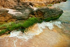 Beautiful sea landscape, closeup of stone on the beach, sea coast with high hills, wild nature stock photography