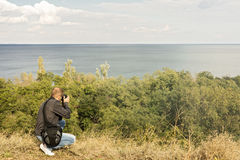 Beautiful sea landscape. A man photographs the sea and the sky. Selective focus Royalty Free Stock Photography