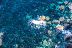 Beautiful sea landscape of some boulders with blue and green water and foam in the rocks royalty free stock photography