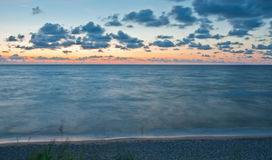 Beautiful sea landscape after a sunset. The quiet sea, clouds float against the pink sky Stock Photo