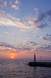 Beautiful sea sunrise and lighthouse on pier Stock Images