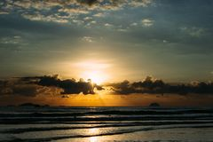Beautiful sea sunrise. Sunset over the sea. Beautiful sunrise by the sea on vacation. The sun`s rays make their way through the clouds. Rolling waves royalty free stock images