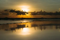 Beautiful sea sunrise. Sunset over the sea. Beautiful sunrise by the sea on vacation. The sun`s rays make their way through the clouds. Rolling waves stock image