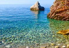 Nice view of the sea. A calm sea by the shore. Clean pebble beach and large stones. The Adriatic. Montenegro royalty free stock image