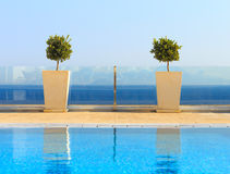 Beautiful sea view from clean swimming pool with plant decoratio Royalty Free Stock Images