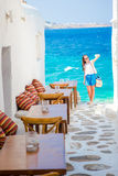 Beautiful sea view in outdoor cafe Mykonos on Cyclades islands. Young woman taking selfie with this amazing view. Benches with pillows in a typical Greek bar in Stock Photo