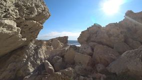 The passage to the sea through the rocks. Beautiful sea view on the rocky shore stock video footage