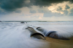 Beautiful sea view scenery over sunrise background. soft waves hitting concrete drainage pipe Royalty Free Stock Photo