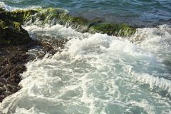 Beautiful sea wave background with green rock shore and foam nea Royalty Free Stock Image