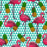 Flamingos and pineapples. Beautiful seamless pattern of pink hand-drawn flamingos and ripe pineapples royalty free illustration